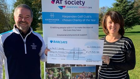 Captains Peter Hart and Cathy Gosling, from Harpenden Golf Club, present the donation to the AT Society