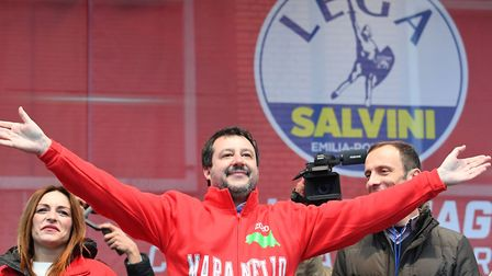 Leader of Italy's far-right League (Lega) party, Matteo Salvini (C) gestures on stage next to centre