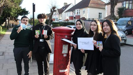 Sixth form students stand next to a post box ready to send their Christmas cards