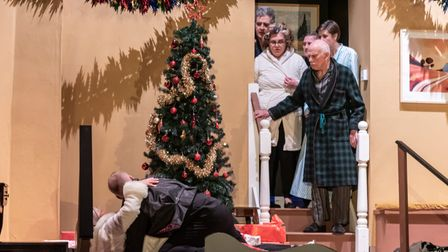 A scene from the play Season's Greetings, a group of people gathered at the top of some steps with one person laid at the...
