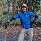 Man with a spade stood in woodland clearing