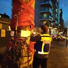 A council worker in high visibility gear posting a paper with notice of the injunction to The Happy Man Tree