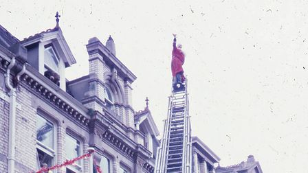 Father Christmas balances on a fully extended ladder outside Rossiters, December 1971