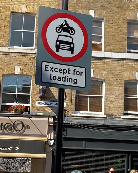 A road sign which shows no cars or motorbikes are allowed in the area except for loading.