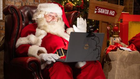 A man dressed as Father Christmas practices making virtual calls to children at the launch of Santa