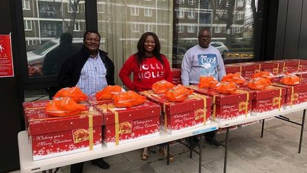 Christ Royal Church members stand in front of a table with Christmas hampers wrapped as gifts in red boxes.