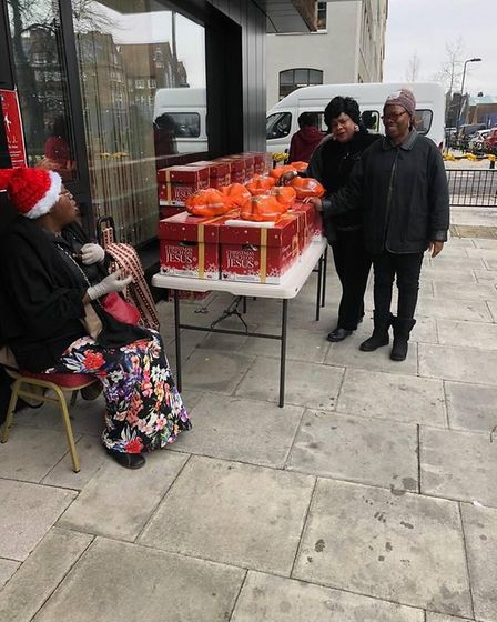 People standing near a table on which free Christmas hampers sit.