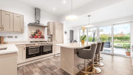 beige kitchen units with central large double ovens with extractor on back wall and central island breakfast bar in the...