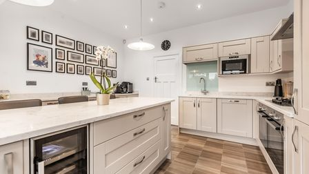 kitchen with beige cupboards and dark-wood laminate flooring with central island with wine cooler and drawers in and...