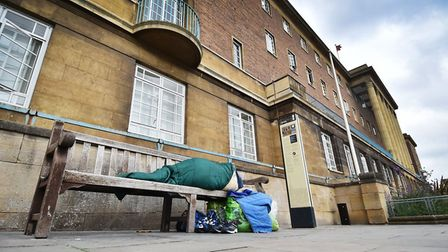 A homeless person sleeping rough on a bench outside Norwich City Hall.
