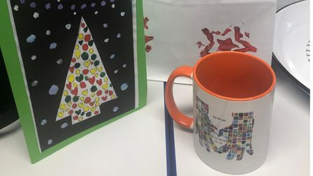 An image showing an attractive mug with mosaic artwork forming a pair of hands, alongside a Christmas card