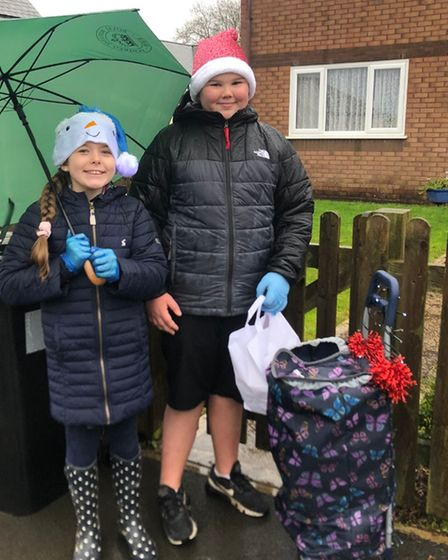 Horwood and Newton Tracey Primary School pupils Kasey and Sam delivering Christmas artwork mugs to their school's...