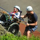 A young boy at Calvert Trust Exmoor learning how to abseil in a wheelchair with an instructor assisting him