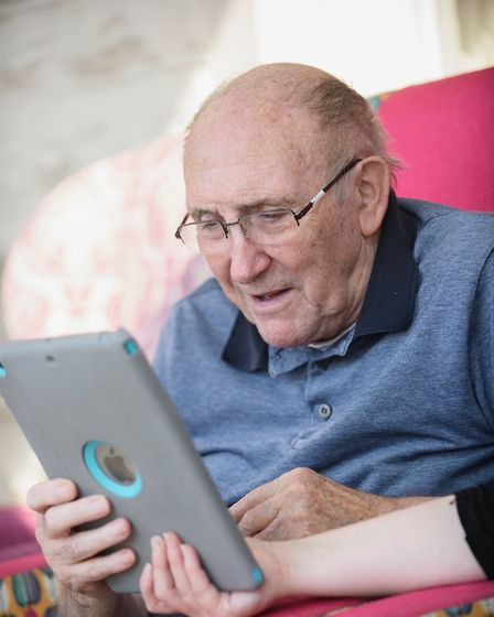 Elderly man using tablet to speak to family and friends