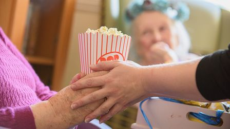 Resident with carer passing popcorn