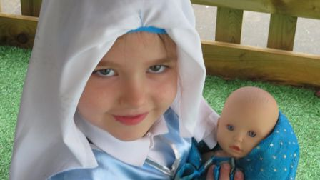 A child dressed as Mary with a doll depicting baby Jesus