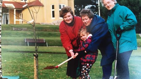 Old family photo from 1993 of people planting a tree in a park