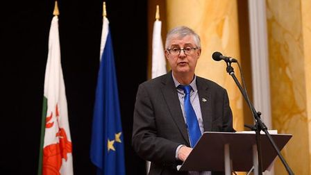 Mark Drakeford appears in front of a European flag. Photograph: CPMR/Flickr.