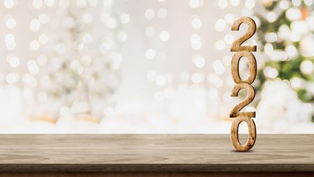 happy new year 2020 at woooden table top with abstract warm living room decor with christmas tree st