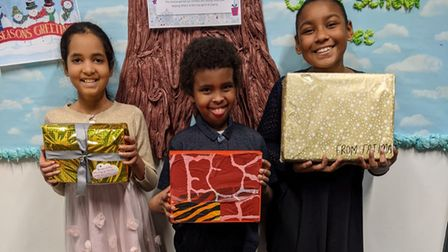 Olive School students holding their gift-wrapped shoe boxes.