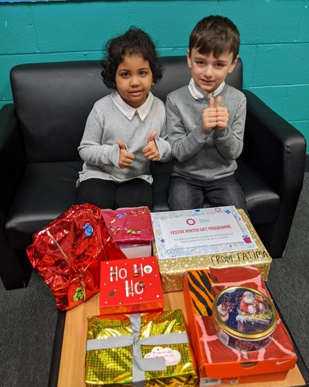 Two students sat next to their shoe box gifts.