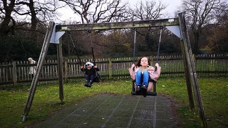 Olivia on the swings with her brother