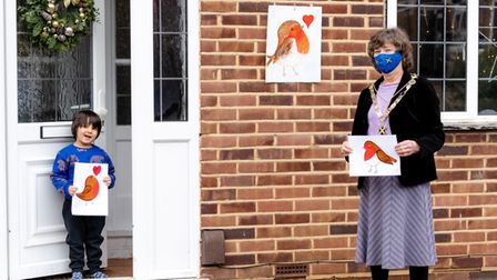 Harrison stands on a doorstep, with the Mayor standing at a distance. Both are holding pictures of robins. The Mayor wears...
