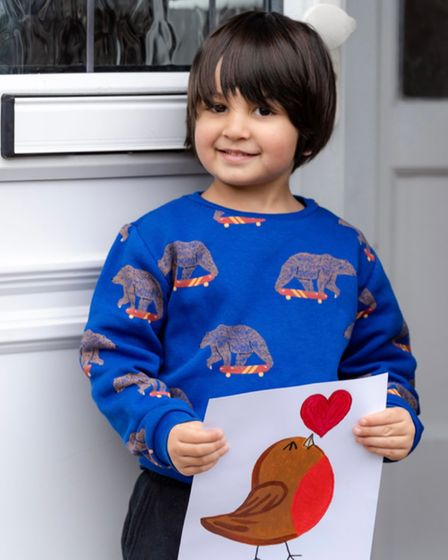 Harrison holds a drawing of a robin on his doorstep, and wears a blue jumper with skateboarding bears on