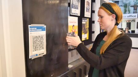 Plough Arts Centre QR code being scanned by a lady with a phone