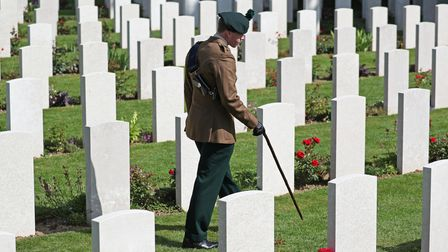 A man in uniform walks past the graves of fallen soldiers during the Royal British Legion's Service