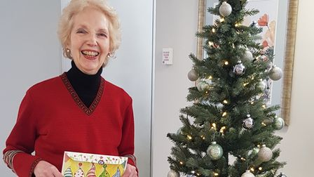 An elderly person holding a Christmas cards, standing next to a Christmas tree