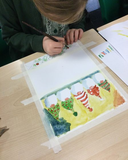 A child colours in a Christmas Card