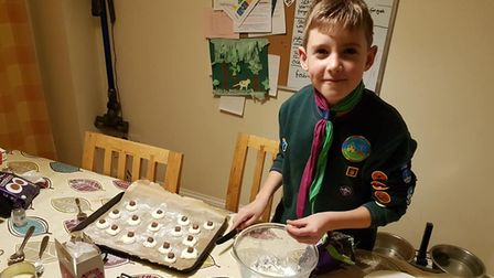 Young person in green top with badges makes sweet treats