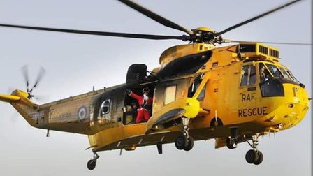 Picture showing Santa waving from yellow Sea King helicopter