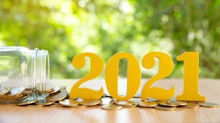 Word 2021 put on coins and glass bottles with coins inside on green bokeh background.Savings New yea