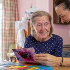 Elderly woman laughing with Bluebird Care carer doing an activity