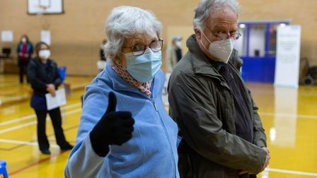 Couple wearing masks, attending vaccination clinic in hall