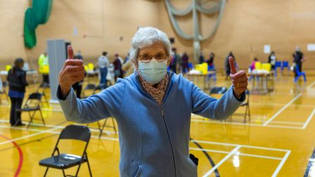 Woman wearing facemask gives thumbs up