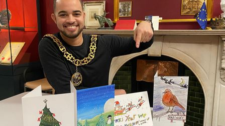 Cllr Adam Jogee, this year's mayor of Haringey, with the four winning Christmas card competition designs.