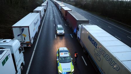 A lorry driver talks to police officers as they patrol along the M20 in Kent where freight traffic i