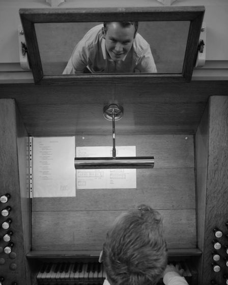 Reflection of organist looking at the photographer while sat down at the organ