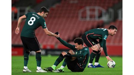 Tottenham Hotspur's Harry Winks lifts team-mate Dele Alli after a foul during the Carabao Cup quarte