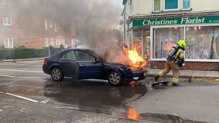 Firefighters using hose reel and breathing apparatus to put out car fire