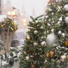 A closeup shot of a Christmas tree with ornaments and covered in snow with a blurred background