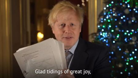 Prime minister Boris Johnson holding up a document believed to be the pages of the Brexit deal during his Christmas message