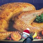 A shopper, wearing a protective facemask and Santa hat, passes a billboard poster featuring a Christ