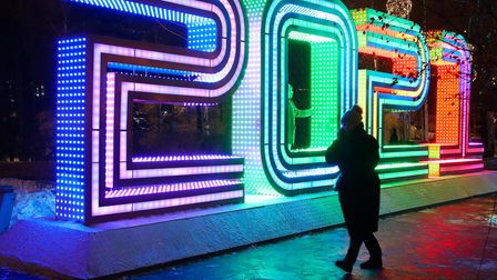 A woman stands next to a light installation set up to spell 2021 at Zaryadye Park, Moscow,ahead of New Year celebrations