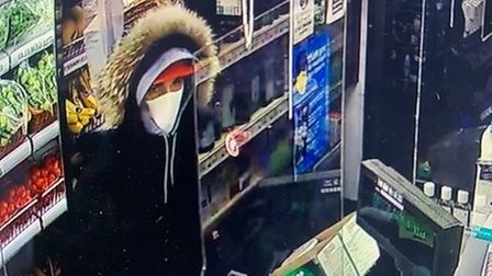 A man in a food and wine shop wearing a red cap, hooded jacket and a mask.