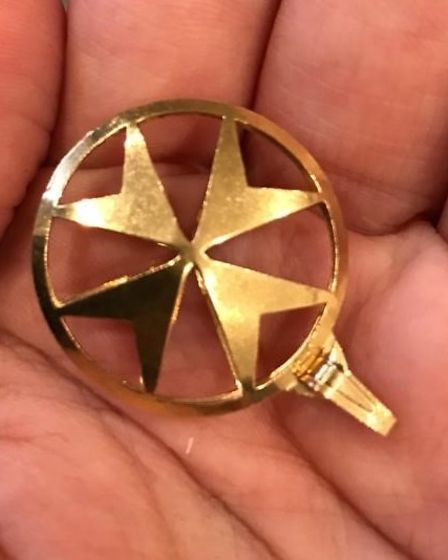 A Maltese gold cross pendant in a cupped hand.
