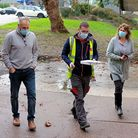 image of people wearing masks carrying a small box of the Covid-19 vaccine to the North Devon Leisure Centre